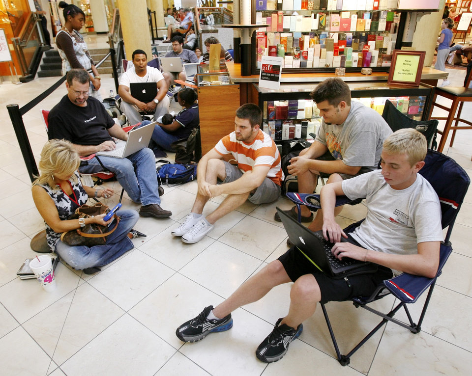 Photo - Clockwise from lower left, Vicki Baldini, Darrell Solomon, Ronald Henderson, Jamila Henderson, holding 8-week-old Ronald Henderson Jr., Jason Stulce, Brandon Jackson, Corbin Jackson and others wait in line to buy the iPhone at the Apple Store in Penn Square Mall in Oklahoma City, Friday, June 29, 2007. The line outside Penn Square Mall began forming at 3:30 a.m. Baldini is the first person in the line. [THE OKLAHOMAN ARCHIVES]