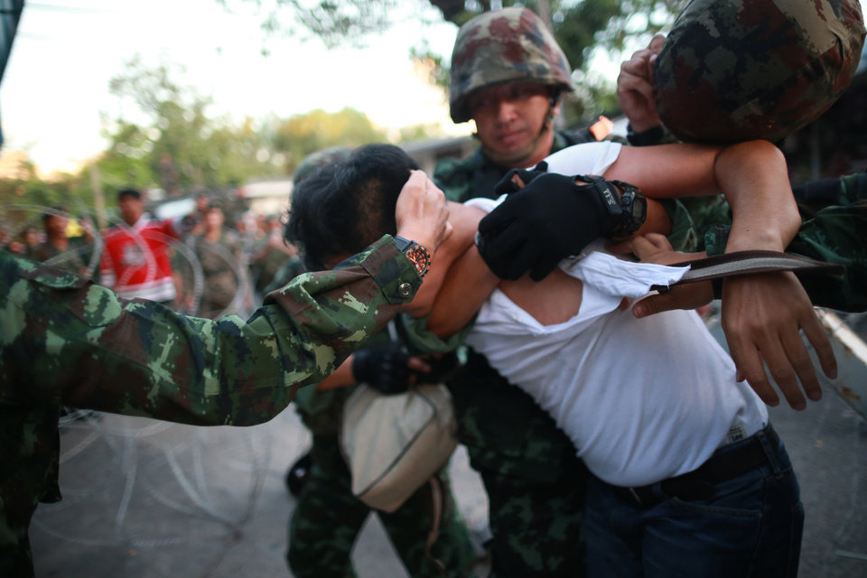 Photo - A protester is detained by Thai soldiers during an anti-coup demonstration at the Victory Monument in Bangkok, Thailand, Saturday, May 24, 2014. Thailand's coup leaders said Saturday that they would keep former Prime Minister Yingluck Shinawatra, Cabinet members and anti-government protest leaders detained for up to a week to give them