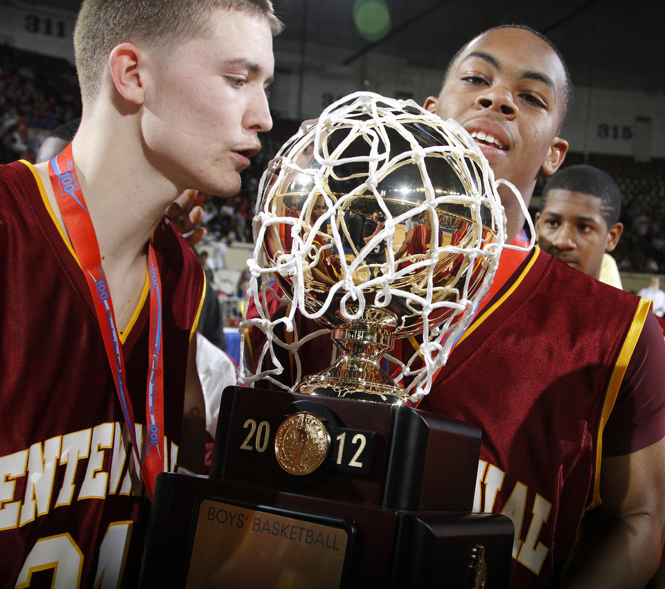 Photo - Centennial's Nicholas Burnett (24) and Prince Thompson (20) hold the championship trophy during the 3A boys State Basketball Championship game between Victory Christian High School and Centennial High School at State Fair Arena on Saturday, March 10, 2012 in Oklahoma City, Okla.  Photo by Chris Landsberger, The Oklahoman