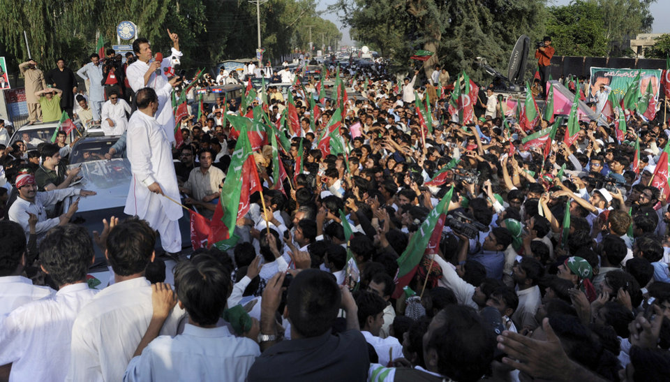 Pakistan's ex-cricket star-turned-politician Imran Khan, top left, addresses supporters during a peace march in Mianwali, Pakistan, Saturday, Oct. 6, 2012. Thousands of Pakistanis joined by a group of U.S. anti-war activists headed toward Pakistan's militant-riddled tribal belt Saturday to protest U.S. drone strikes - even as a Pakistani Taliban faction warned that suicide bombers would stop the demonstration. (AP Photo/Jabbar Ahmed)