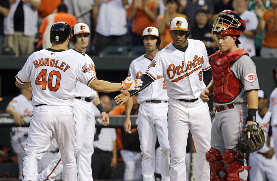 Photo - Baltimore Orioles' Nick Hundley (40) crosses home plate in front of Cincinnati Reds catcher Tucker Barnhart, right, after hitting a three-run home run in the first inning of an interleague baseball game, Thursday, Sept. 4, 2014, in Baltimore. Baltimore's Kelly Johnson, second from left, J.J. Hardy and Jonathan Schoop (6) look on. (AP Photo/Patrick Semansky)