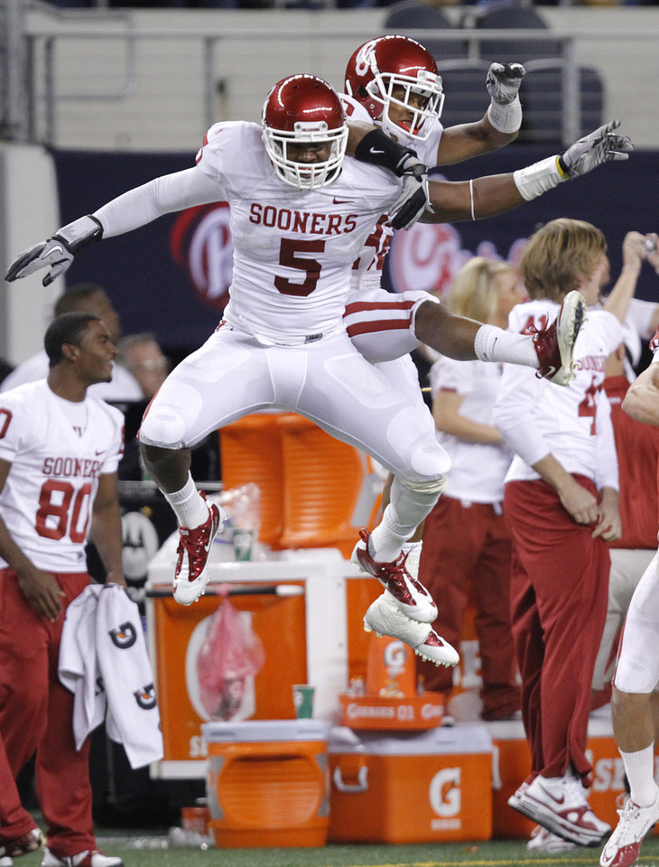 Photo - Oklahoma's Joseph Ibiloye (5) and Jamell Fleming (32) celebrate after stopping Nebraska on fourth down during the Big 12 football championship game between the University of Oklahoma Sooners (OU) and the University of Nebraska Cornhuskers (NU) at Cowboys Stadium on Saturday, Dec. 4, 2010, in Arlington, Texas.  Photo by Chris Landsberger, The Oklahoman