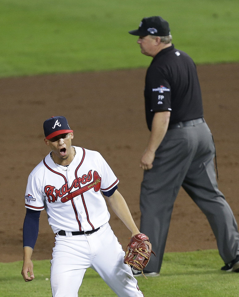 Photo - Atlanta Braves shortstop Andrelton Simmons, left, cheers after tagging out Los Angeles Dodgers' Dee Gordon who was trying to steal second base in the ninth inning of Game 2 of the National League division series on Friday, Oct. 4, 2013, in Atlanta. The Braves won 4-3. (AP Photo/Mike Zarrilli)
