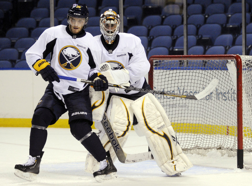 Photo - Buffalo Sabres' Mikhail Grigorenko, of Russia, gets bumped by goalie Ryan Miller in front of the crease during the first day of NHL hockey training camp in Buffalo, New York, Sunday, Jan. 13, 2013. (AP Photo/Gary Wiepert)
