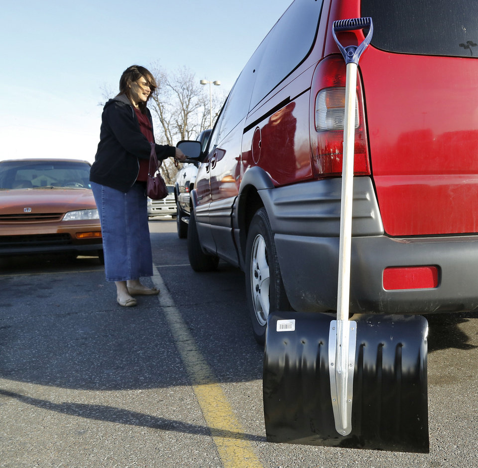 Photo - Tabitha Burgett unlocks her vehicle after carrying  the snow shovel she just purchased to her van in the parking lot of the Westlake Ace Hardware store at SW 44 and Western on Wednesday afternoon, Dec. 4, 2013. Burgett said the shovel was a top priority on her list as she and her husband prepared for an approaching winter storm. She and her husband had talked about the need to buy a snow shovel for a number of weeks but neither had made the purchase.  She said in addition to her trip to the hardware store, she was making a stop at the grocery store.  She and her husband and their five children live in south Oklahoma City. Burgett said when the winter weather arrives, her family will most likely just stay inside their home where it will be cozy and warm.  Jim Robinson, a manager at the store, said a number of customers have purchased shovels and scrapers, but he reported even higher sales of tube sand and ice melt. Photo by Jim Beckel, The Oklahoman