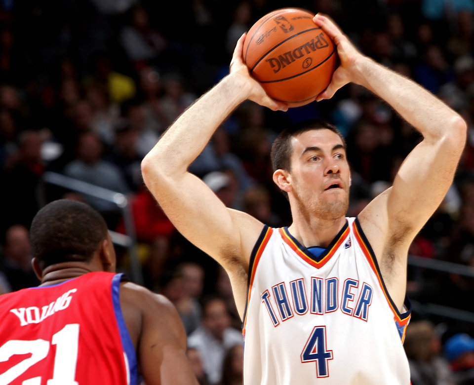 Photo - Oklahoma City's Nick Collison looks for an open teammate against Philadelphia's defense during the second half of their NBA basketball game at the Ford Center in Oklahoma City on Tuesday, Dec. 2, 2009. The Thunder beat the 76ers 117 to 106. By John Clanton, The Oklahoman