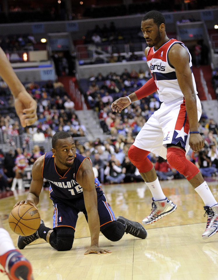 Photo - Charlotte Bobcats guard Kemba Walker (15) dribbles the ball against Washington Wizards point guard John Wall during the first half of an NBA basketball game, Saturday, March 9, 2013, in Washington. (AP Photo/Nick Wass)