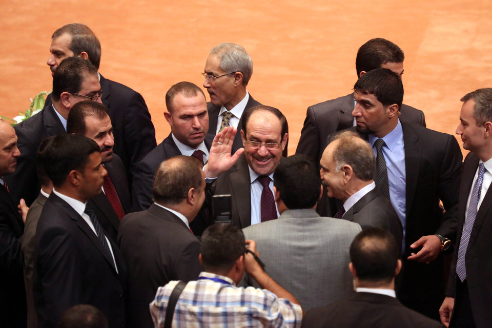 Photo - Iraqi Prime Minister Nouri al-Maliki, center, greets lawmakers at the first session of the newly elected parliament in the heavily fortified Green Zone in Baghdad, Iraq, Tuesday, July 1, 2014. Iraq's new parliament ended its inaugural session Tuesday after failing to make any progress in choosing a new prime minister even as the country faces a militant blitz that threatens to rip it apart and a spike in violence that made June the deadliest month in at least two years. (AP Photo/Hadi Mizban)