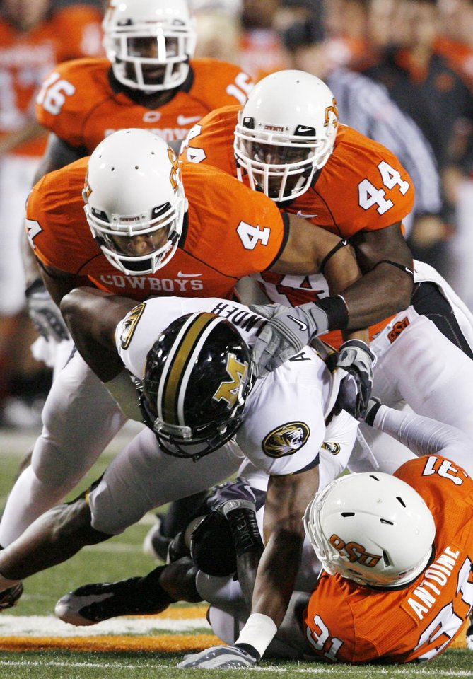 Photo - Cowboys mob Danario Alexander including Perrish Cox (16), Patrick Levine (4), Donald Booker (44) and Lucien Antoine (31) during the college football game between Oklahoma State University (OSU) and the University of Missouri (MU) at Boone Pickens Stadium in Stillwater, Okla. Saturday, Oct. 17, 2009.  Photo by Steve Sisney, The Oklahoman ORG XMIT: KOD