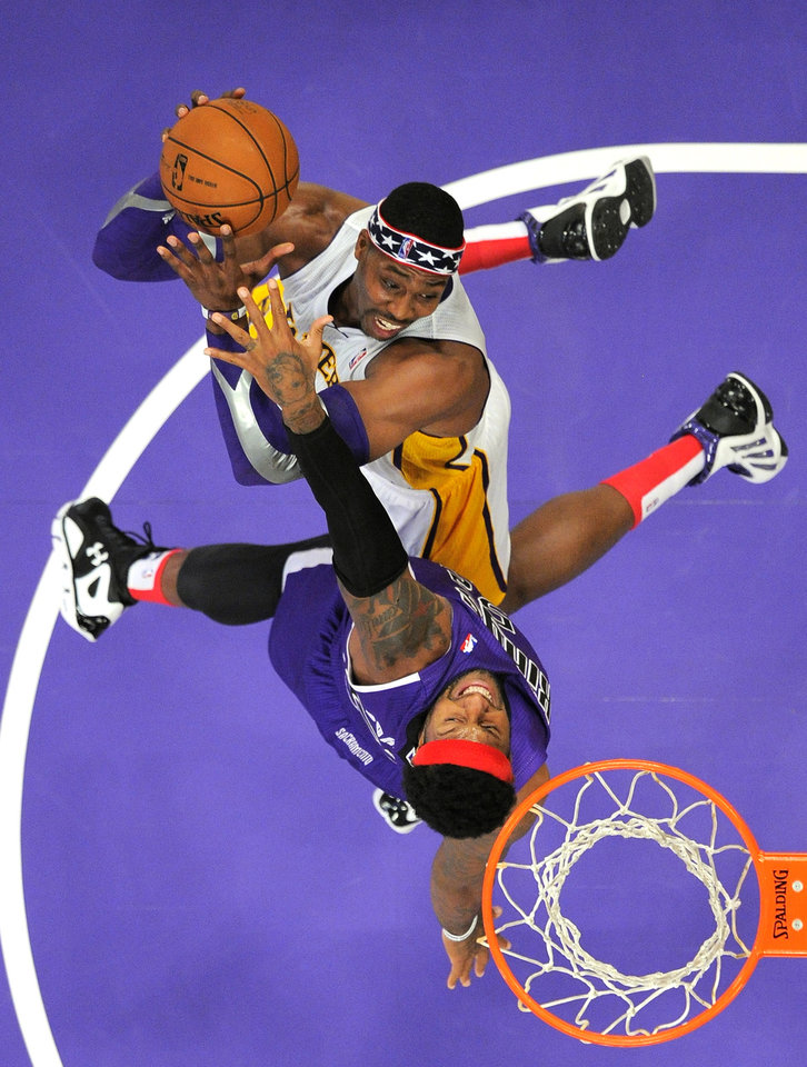 Los Angeles Lakers center Dwight Howard, top, puts up a shot as Sacramento Kings forward James Johnson defends during the first half of their NBA basketball game, Sunday, Nov. 11, 2012, in Los Angeles. (AP Photo/Mark J. Terrill)