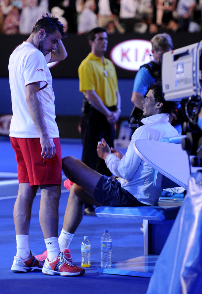 Photo - Stanislas Wawrinka of Switzerland, left, talks with Rafael Nadal of Spain before the trophy presentation, following his win in the men's singles final at the Australian Open tennis championship in Melbourne, Australia, Sunday, Jan. 26, 2014. (AP Photo/Andrew Brownbill)