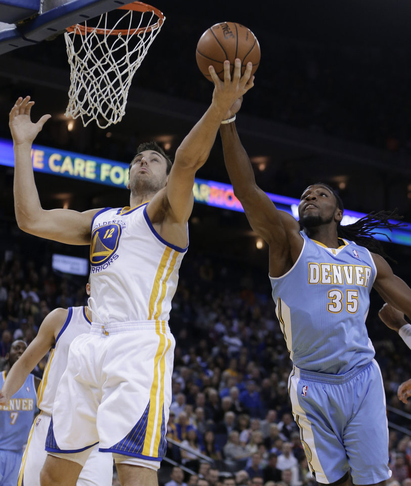 Photo - Denver Nuggets' Kenneth Faried, right, and Golden State Warriors' Andrew Bogut (12) reach for a rebound during the first half of an NBA basketball game on Wednesday, Jan. 15, 2014, in Oakland, Calif. (AP Photo/Ben Margot)