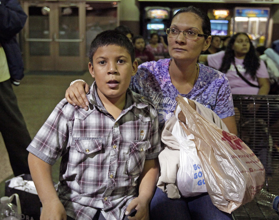 Photo - Maria Eva Casco, left, and her son Christian Casco of El Salvador, sit at at the Greyhound bus terminal, Thursday, May 29, 2014 in Phoenix. About 400 mostly Central American women and children caught crossing from Mexico into south Texas were flown to Arizona this weekend after border agents there ran out of space and resources.  Officials then dropped hundreds of them off at Phoenix and Tucson Greyhound stations, overwhelming the stations and humanitarian groups who were trying to help. (AP Photo/Rick Scuteri)
