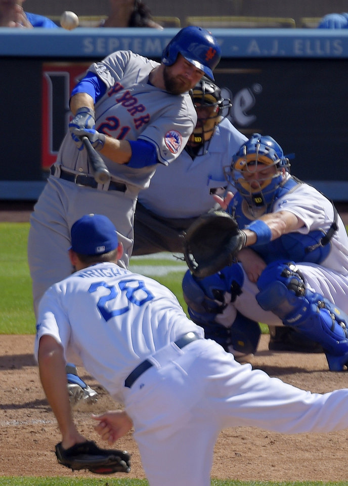 Photo - New York Mets' Lucas Duda, top left, hits a solo home run as Los Angeles Dodgers relief pitcher Jamey Wright, bottom, and catcher Drew Butera, top right, looks on along with home plate umpire Dale Scott during the ninth inning of a baseball game, Sunday, Aug. 24, 2014, in Los Angeles. (AP Photo/Mark J. Terrill)