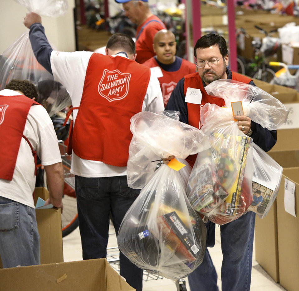 Scores of volunteers stayed busy inside the former Penney\'s store at Crossroads Mall loading bags of gifts and toys into shopping carts so they can be delivered to clients. The Salvation Army and Feed the Children teamed to distribute bicycles and toys for children, and handed out boxes of food for families at their annual distribution event Wednesday, Dec. 19, 2012. Salvation Army officials said 100 volunteers helped make the event go smoothly. The volunteers loaded bags of toys and bikes into vehicles of clients who had been pre-approved for assistance. Many of the gifts were provided through the Salvation Army\'s Angel Tree program Photo by Jim Beckel, The Oklahoman