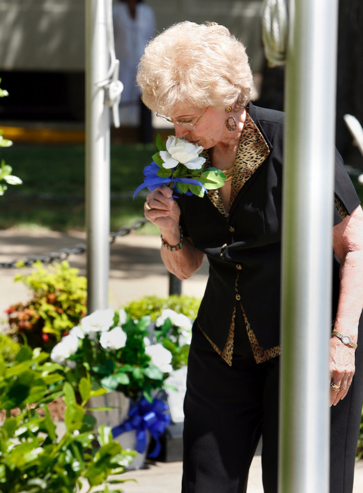 Photo - June Armstrong, youngest daughter of fallen officer Webb Campbell, takes her turn laying flowers at a memorial for fallen officers as they are remembered at a service in front of Oklahoma City Police Headquarters in Oklahoma City, Oklahoma on Friday, May 9, 2008.  Armstrong and two sisters take turns with the duty each year.  Their father Webb Campbell was killed in 1938 BY STEVE SISNEY, THE OKLAHOMAN    ORG XMIT: KOD