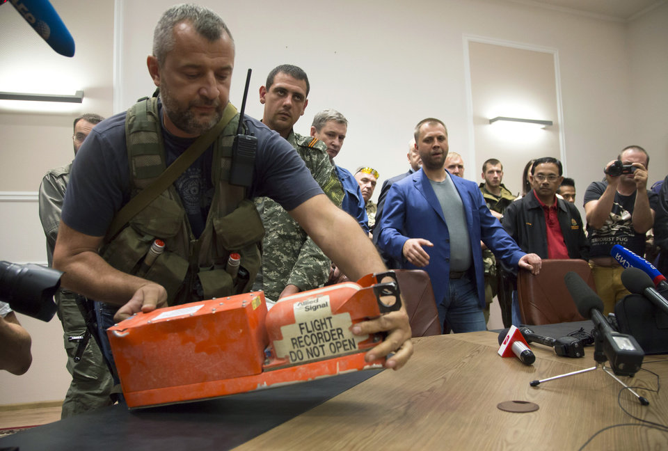 Photo - A pro-Russian fighter places a black box from the crashed Malaysia Airlines Flight 17 on a table while handing it over from Donetsk People's Republic officials to Malaysian representatives in the city of Donetsk, eastern Ukraine Tuesday, July 22, 2014. Bowing to international pressure Monday, pro-Moscow separatists released a train packed with bodies and handed over the black boxes from the downed Malaysia Airlines plane, four days after it plunged into rebel-held eastern Ukraine. (AP Photo/Dmitry Lovetsky)