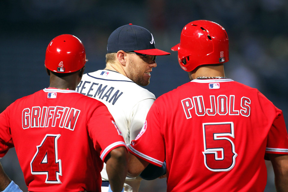 Photo - Los Angeles Angels' Albert Pujols (5) talks with Atlanta Braves first baseman Freddie Freeman (5) and first base coach Alfredo Griffin (4) after hitting a single in the third inning inning of a baseball gam,e Sunday, June 15, 2014, in Atlanta. (AP Photo/Todd Kirkland)