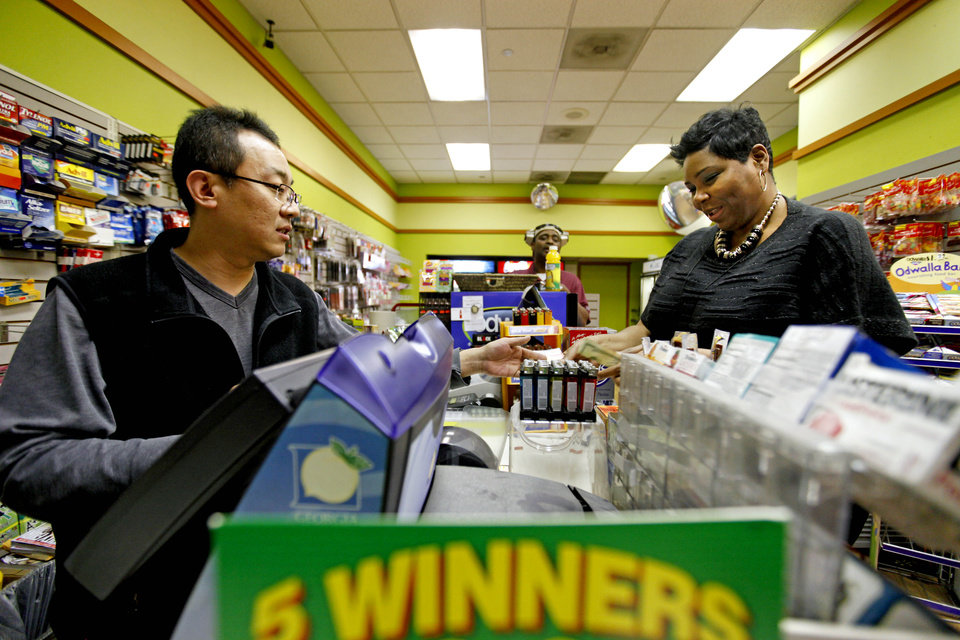 Photo - Benita Lewis, 41, of Atlanta, right, buys a Powerball lottery ticket from store worker Bryant Kim, at a convenience store, Wednesday, Nov. 28, 2012, in Atlanta.