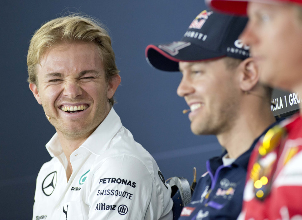 Photo - World Cup leader and Mercedes Formula One driver Nico Rosberg of Germany smiles besides Red Bull Formula One driver Sebastian Vettel of Germany and Ferrari Formula One driver Kimi Raikkoenen of Finland, from left to right, during a press conference in Hockenheim, Germany, Thursday, July 17, 2014. The German Grand Prix will be held on Sunday, July 20, 2014. (AP Photo/Jens Meyer)