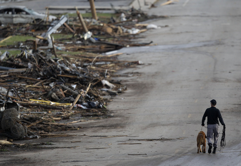 Photo - A rescue worker walks past debris at Joplin High School, which was severely damaged by a tornado in Joplin, Mo., Monday, May 23, 2011. A large tornado moved through much of the city Sunday, damaging a hospital and hundreds of homes and businesses and killing at least 89 people. (AP Photo/Charlie Riedel) ORG XMIT: MOCR208