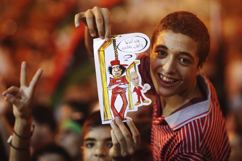 "A boy holds a drawing depicting Moammar Gadhafi and his son Seif al-Islam being hanged during celebrations of the capture in Tripoli of the son at the rebel-held town of Benghazi, Libya, early Monday, Aug. 22, 2011. Libyan rebels raced into Tripoli Sunday and met little resistance as Gadhafi's defenders melted away and his 42-year rule rapidly crumbled. The words on the caricature reads ""Did we already take Benghazi?"" (AP Photo/Alexandre Meneghini)"