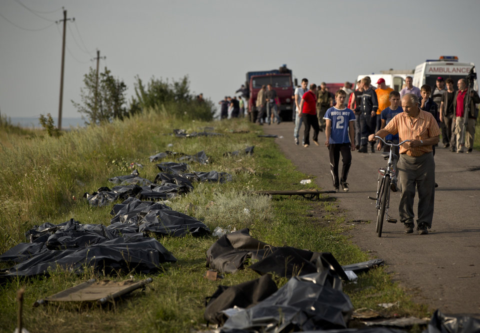 Photo - Bodies of victims are placed in plastic sacks by the side of the road at the crash site of Malaysia Airlines Flight 17 near the village of Hrabove, eastern Ukraine, Saturday, July 19, 2014. World leaders demanded Friday that pro-Russia rebels who control the eastern Ukraine crash site of Malaysia Airlines Flight 17 give immediate, unfettered access to independent investigators to determine who shot down the plane. (AP Photo/Vadim Ghirda)