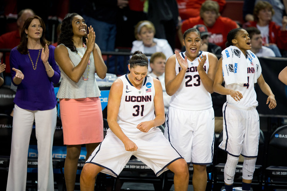 Photo - Connecticut's Stefanie Dolson (31) does a victory dance as teammates Kaleena Mosqueda-Lewis (23) and Moriah Jefferson (4) celebrate their win of a regional final game in the NCAA college basketball tournament in Lincoln, Neb., Monday, March 31, 2014.  Connectiut defeated Texas A&M 69-54. (AP Photo/The Omaha World-Herald/Matt Miller)