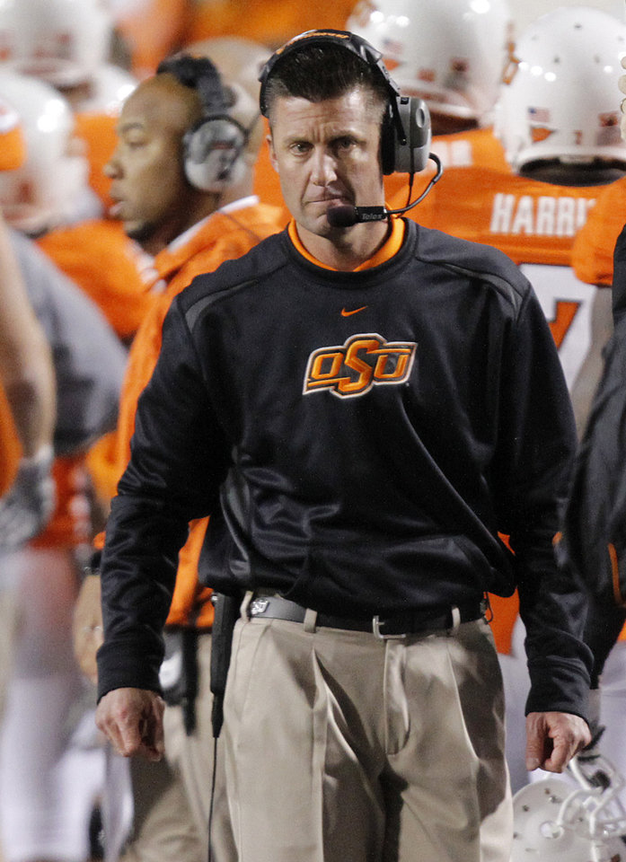 Photo - OSU coach Mike Gundy walks the sideline during the Bedlam college football game between the University of Oklahoma Sooners (OU) and the Oklahoma State University Cowboys (OSU) at Boone Pickens Stadium in Stillwater, Okla., Saturday, Nov. 27, 2010. Photo by Chris Landsberger, The Oklahoman