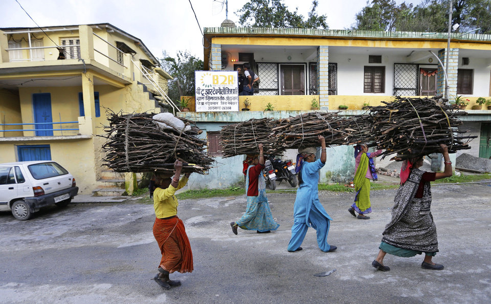 Photo -   In this Aug. 23, 2012 photo, women carrying bundles of wood on their head walk past the offices of B2R in Simayal, India. Before B2R arrived in Simayal, local women had little option but to marry right out of school, and educated young men had to travel far to seek respectable jobs. (AP Photo/Saurabh Das)