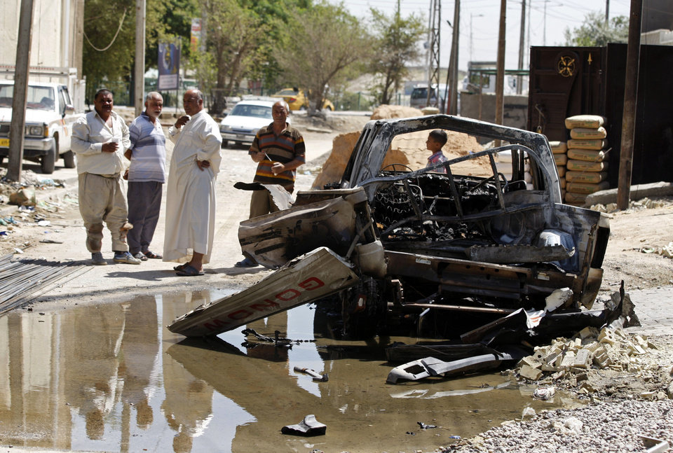 Photo - Civilians inspect the aftermath of a car bomb attack in Baghdad, Iraq, Wednesday, July 24, 2013. A bomb exploded near a Sunni mosque in Baghdad's southern Dora neighborhood on Tuesday, killing several people and wounding many more,  police said. (AP Photo/Karim Kadim)