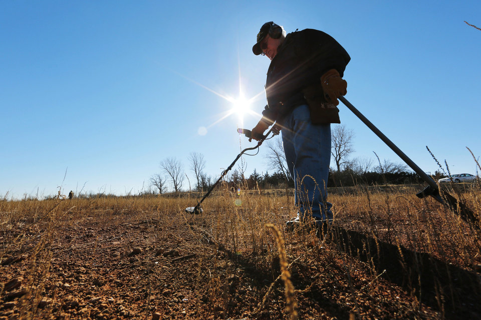 Larry Dobbs uses a metal detector Thursday as he looks for lost items at Lake Hefner in Oklahoma City. Area lakes are very low because of the recent drought.