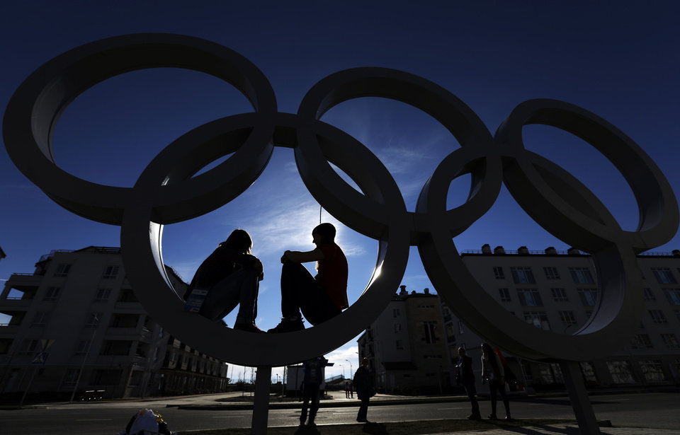 Photo - Anne Konschak, left, and Germany athlete Ivonne Schroeder pose for a picture inside some Olympic rings in the Olympic Village at the 2014 Winter Olympics, Wednesday, Feb. 12, 2014, in Sochi, Russia. (AP Photo/Morry Gash)