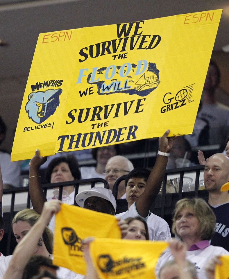 Photo - A Memphis Grizzlies fan holds a sign referring to the recent Mississippi River flood during the second half of Game 6 against the Oklahoma City Thunder in a second-round NBA basketball playoff series on Friday, May 13, 2011, in Memphis, Tenn. The Grizzlies won 95-83 to even the series 3-3. (AP Photo/Wade Payne)