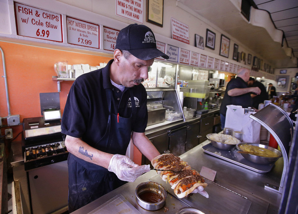 Photo - TAKES OUT HOT DOG REFERENCE -In this Monday, March 3, 2014 photo  Sal O'Brien holds wieners he preps