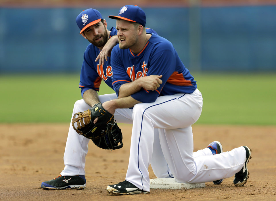 Photo - New York Mets' Ike Davis, left, and Lucas Duda kneel on first base while watching teammates participate in a fielding drill during spring training baseball practice Saturday, Feb. 22, 2014, in Port St. Lucie, Fla. (AP Photo/Jeff Roberson)