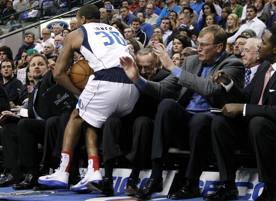 Photo -   Dallas Mavericks' Dahntay Jones (30) chases a ball out of bounds and falls into the lap of Minnesota Timberwolves head coach Rick Adelman as members of the coaching staff watch during the first half of an NBA basketball game, Monday, Nov. 12, 2012, in Dallas. (AP Photo/Tony Gutierrez)