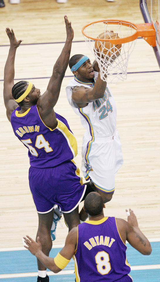 Photo - Desmond Mason of the Hornets scores betweeen Kwame Brown and Kobe Bryant of the Los Angeles Lakers during the New Orleans/Oklahoma City Hornets NBA basketball game against the Lakers at the Ford Center in Oklahoma City, Feb. 4, 2006.  By Bryan Terry/The Okahoman