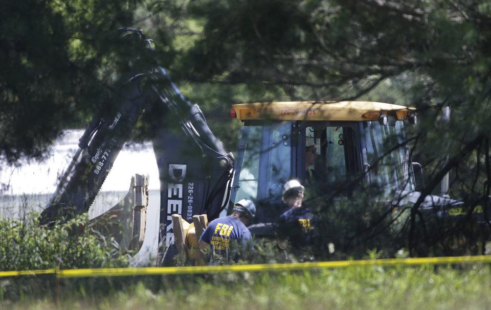 Photo - Members of an FBI evidence response team look over an area being cleared in Oakland Township, Mich., Tuesday, June 18, 2013 where officials continue the search for the remains of Teamsters union president Jimmy Hoffa, who disappeared from a Detroit-area restaurant in 1975. (AP Photo/Carlos Osorio)