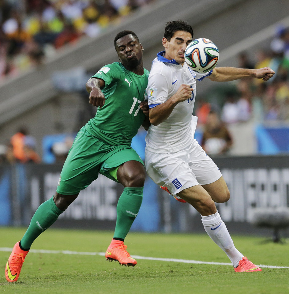 Photo - Ivory Coast's Serge Aurier pushes off Greece's Lazaros Christodoulopoulos during the group C World Cup soccer match between Greece and Ivory Coast at the Arena Castelao in Fortaleza, Brazil, Tuesday, June 24, 2014. (AP Photo/Bernat Armangue)