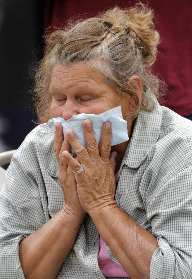 Photo - Christine Cortez holds a temporary bandage to her mouth as dentists get gauze for her mouth after she had five of her teeth extracted.  Today is Cortez' first time to receive treatment  from this volunteer medical group. Remote Area Medical Volunteer Corps, the two-day health care event brought dozens of local health providers to State Fair Park in Oklahoma City on Saturday, Aug. 25, 2012,  to provide free services for some of the state's neediest residents.   An estimated 1,000 people received  free dental, vision, mental health and general health treatment at  the two-day event, according to Ron Brewer, director of the volunteer medical group.  Free health care will again be offered  on Sunday.    Photo by Jim Beckel, The Oklahoman.