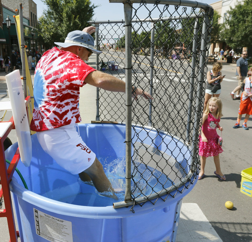 Photo -  Mike Thompson takes a plunge into a dunk tank after a throw from Reese Campbell, 5, during the annual Krazy Daze celebration in downtown Edmond. PHOTO BY PAUL HELLSTERN, THE OKLAHOMAN   PAUL HELLSTERN -