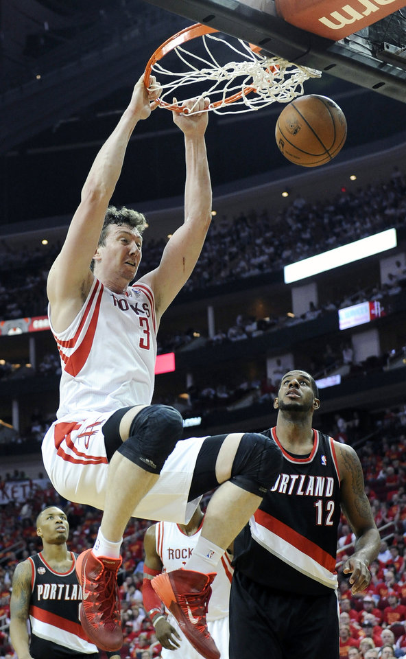 Photo - Houston Rockets' Omer Asik (3) dunks the ball over Portland Trail Blazers' LaMarcus Aldridge (12) in the second half of Game 5 of an opening-round NBA basketball playoff series Wednesday, April 30, 2014, in Houston. The Rockets won 108-98 to send the teams back to Portland for Game 6. (AP Photo/Pat Sullivan)