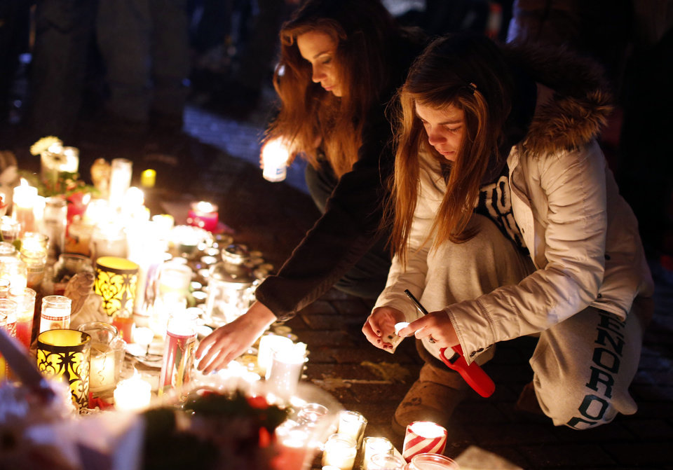 Photo - Visitors light candles at a memorial to shooting victims, Monday, Dec. 17, 2012, in Newtown, Conn. A gunman walked into Sandy Hook Elementary School in Newtown Friday and opened fire, killing 26 people, including 20 children. (AP Photo/Jason DeCrow) ORG XMIT: CTJD121