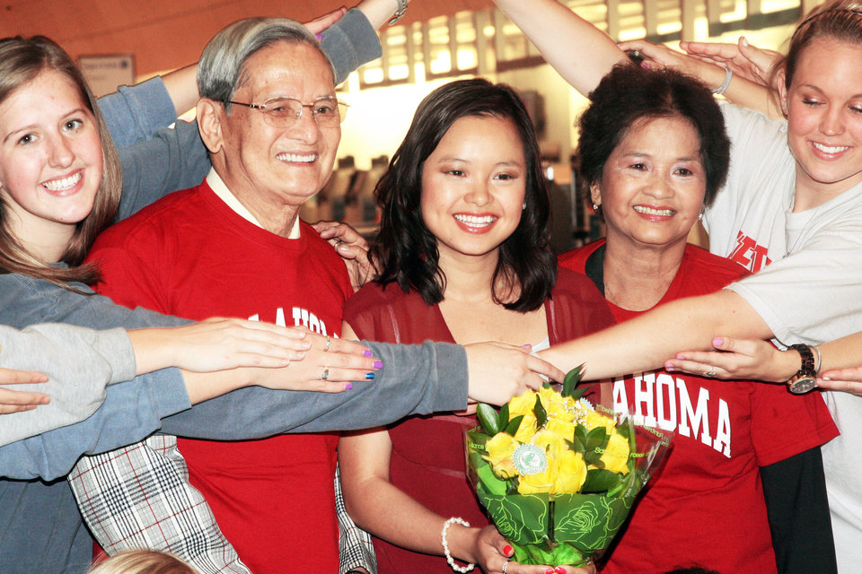 Photo - Tri Delta sorority members surround Hoan Doan, Chinh Doan and Tu Tran on Monday as the family is reunited at Will Rogers World Airport in Oklahoma City. Photo by Ashley R. West, for The Oklahoman