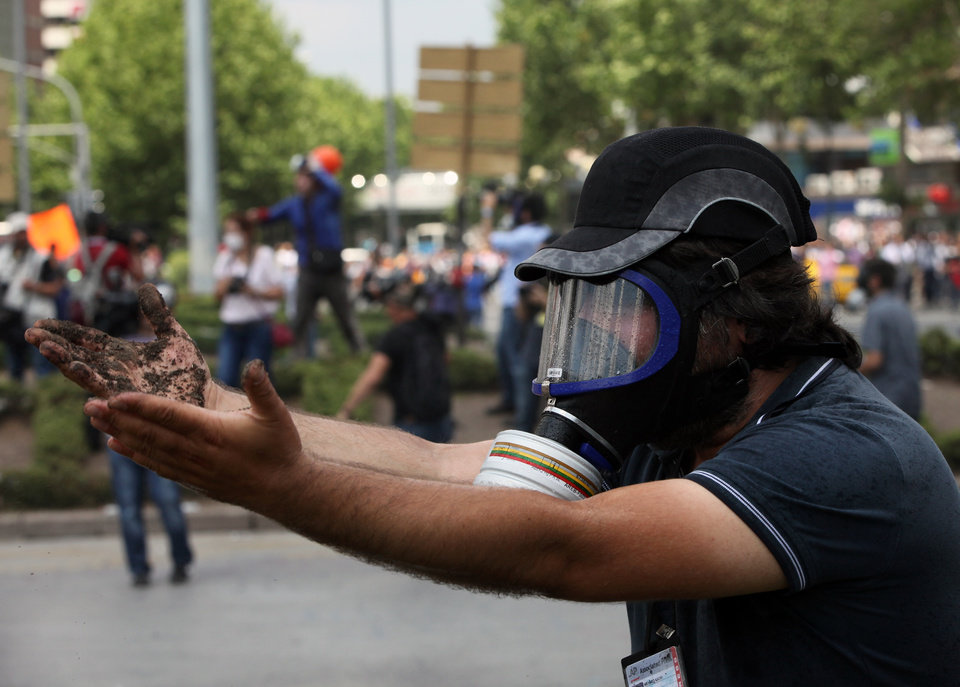 Photo - A Turkish journalist reacts after riot police sprayed water cannon at journalists together with protesters who remained defiant after authorities evicted activists from an Istanbul park, making clear they are taking a hardline against attempts to rekindle protests that have shaken the country, in city's main Kizilay Square in Ankara, Turkey, Sunday, June 16, 2013.(AP Photo/Burhan Ozbilici)