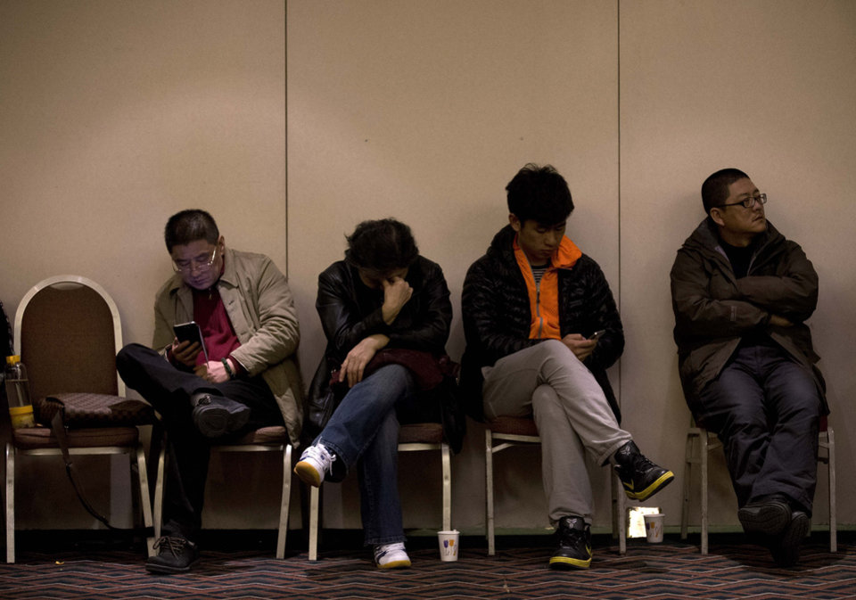 Photo - Relatives of Chinese passengers aboard the missing Malaysia Airlines Flight MH370 wait for a news briefing held by the airlines' officials at a hotel ballroom in Beijing Monday, March 17, 2014. The search for the missing Malaysian jet pushed deep into the northern and southern hemispheres Monday as Australia took the lead in scouring the seas of the southern Indian Ocean and Kazakhstan - about 10,000 miles to the northwest - answered Malaysia's call for help in the unprecedented hunt. (AP Photo/Andy Wong)