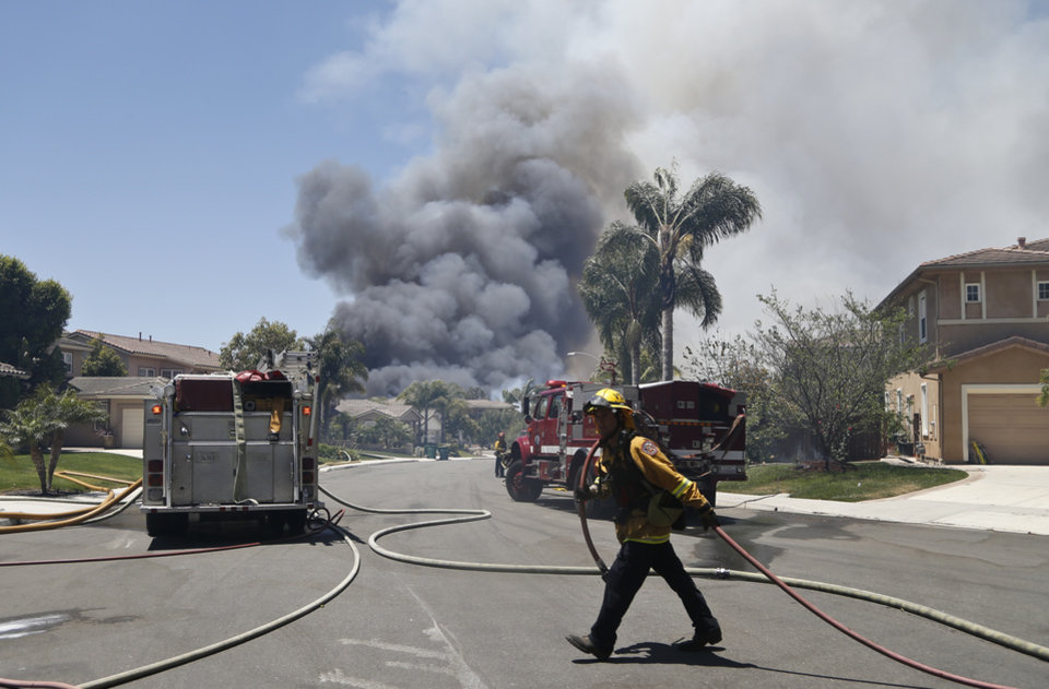 Photo - A fireman drags a hose as smoke rises from a nearby wildfire Wednesday, May 14, 2014, in Carlsbad, Calif. Carlsbad city officials said mandatory evacuations were in progress Wednesday, and more than 11,000 notices were sent to homes and businesses.  (AP Photo)