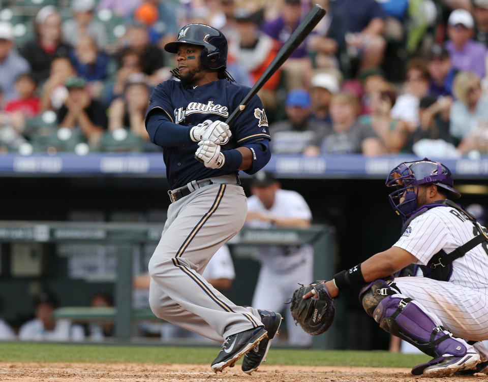 Photo - Milwaukee Brewers' Rickie Weeks, left, singles as Colorado Rockies catcher Wilin Rosario covers in the fifth inning of a baseball game in Denver, Sunday, June 22, 2014. (AP Photo/David Zalubowski)