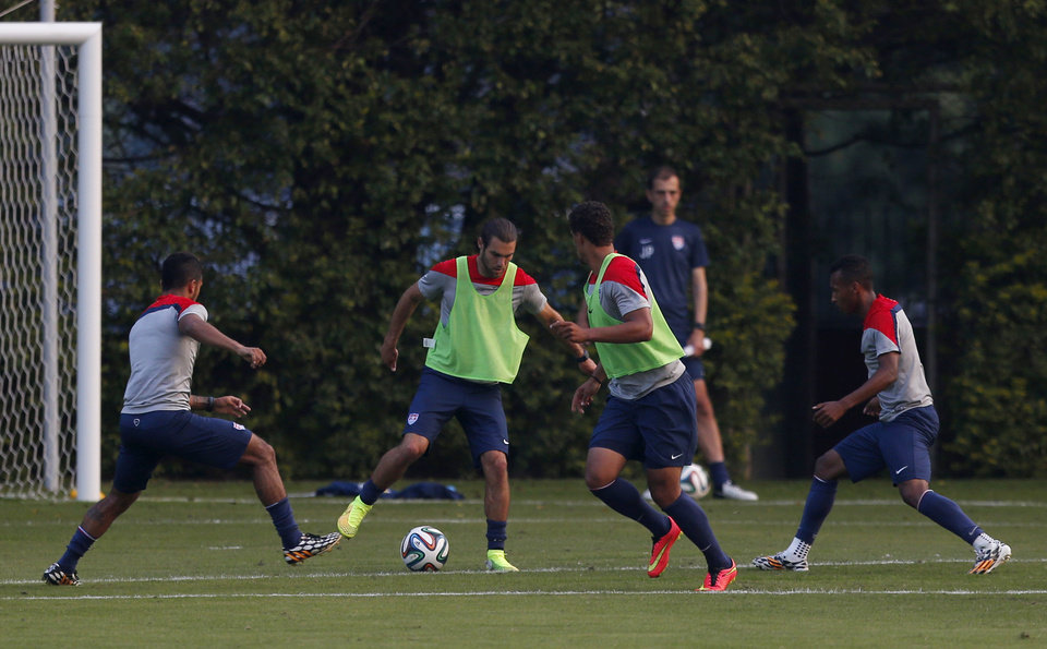 Photo - United States' Graham Zusi, center left, controls the ball during a training session in Sao Paulo, Brazil, Tuesday, June 17, 2014.  The United States will play against Portugal in group G of the 2014 soccer World Cup on June 22. (AP Photo/Julio Cortez)